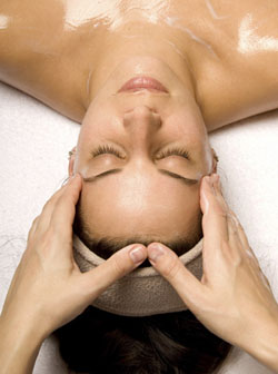 woman getting a head massage with cream in a spa